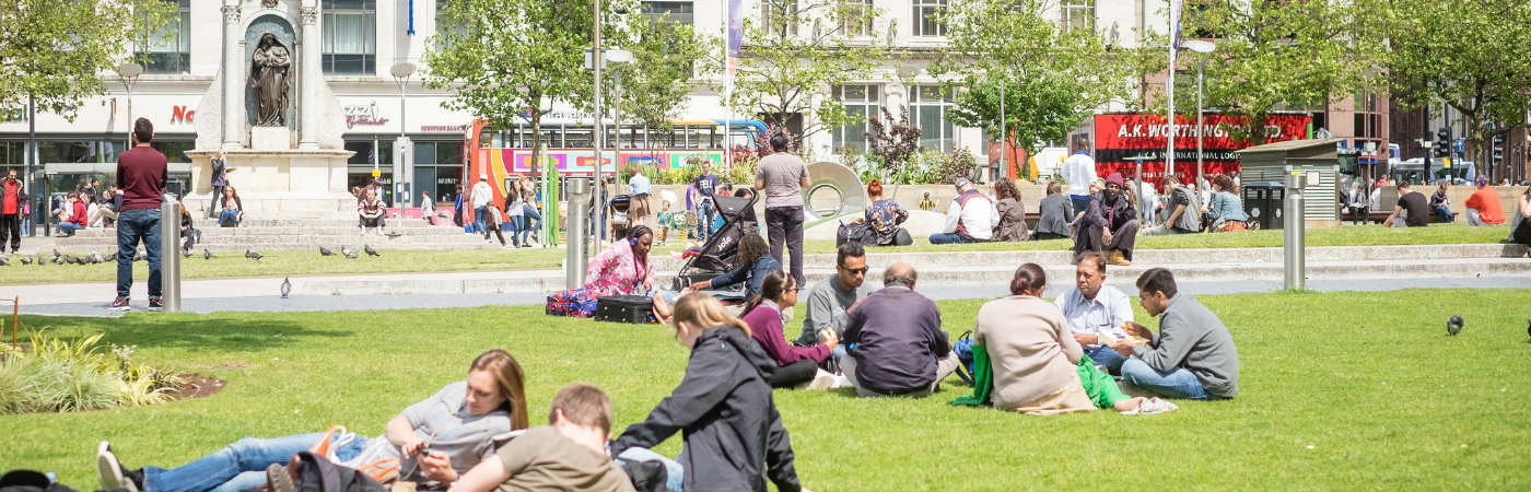 People enjoying the sunshine in Manchester's Piccadilly Gardens