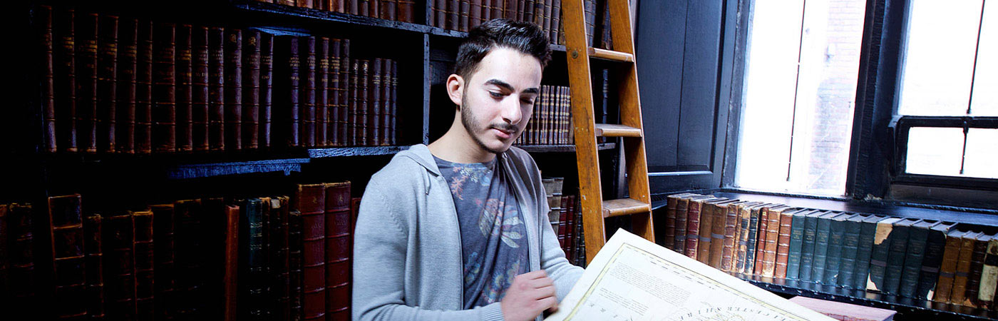 Student examining maps in Cheetham Library