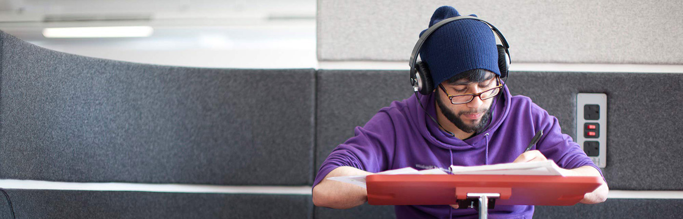 Student with headphones on working at a laptop