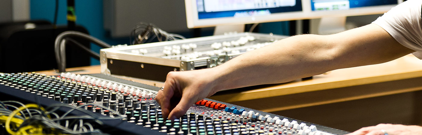 Students adjusting levels of a mixing desk