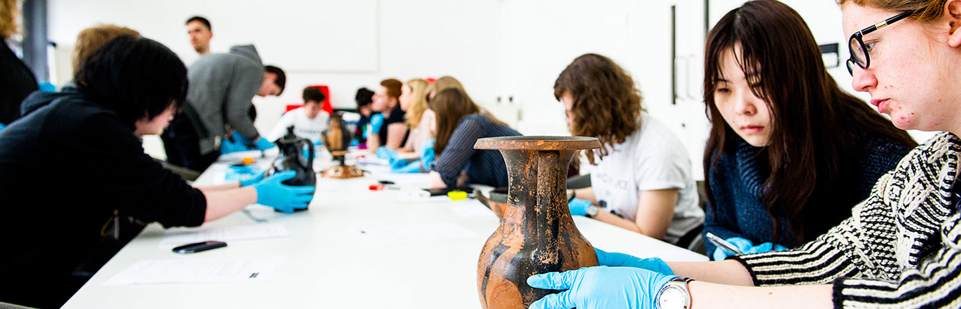 Students examining ancient urns