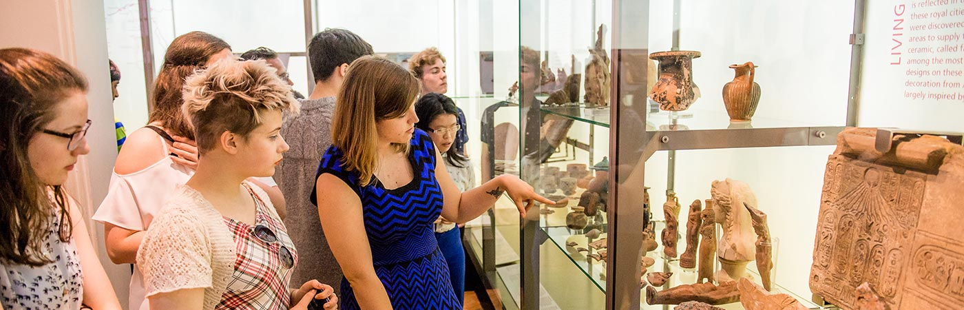 Students in a museum looking at middle eastern artifacts