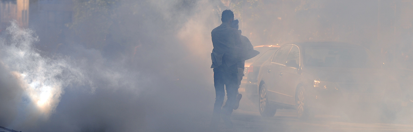 A man runs through a smoke screen as part of a protest