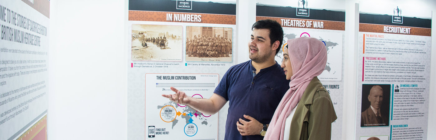 Two history students talking by a wall display