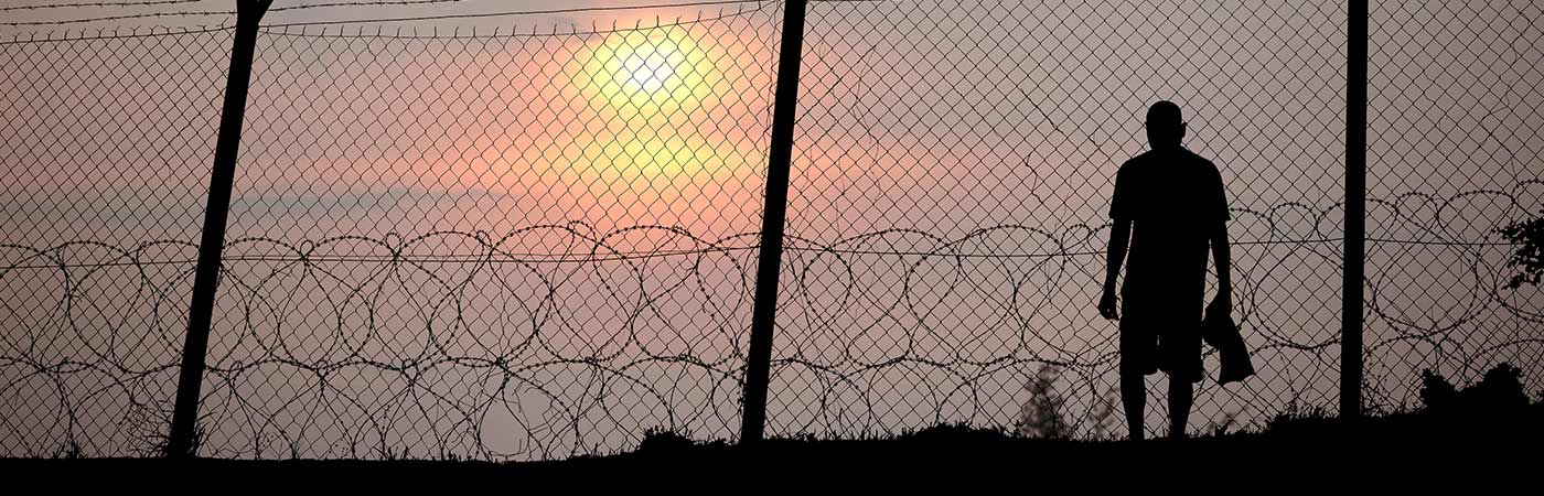 Human figure silhouetted behind barbed wire