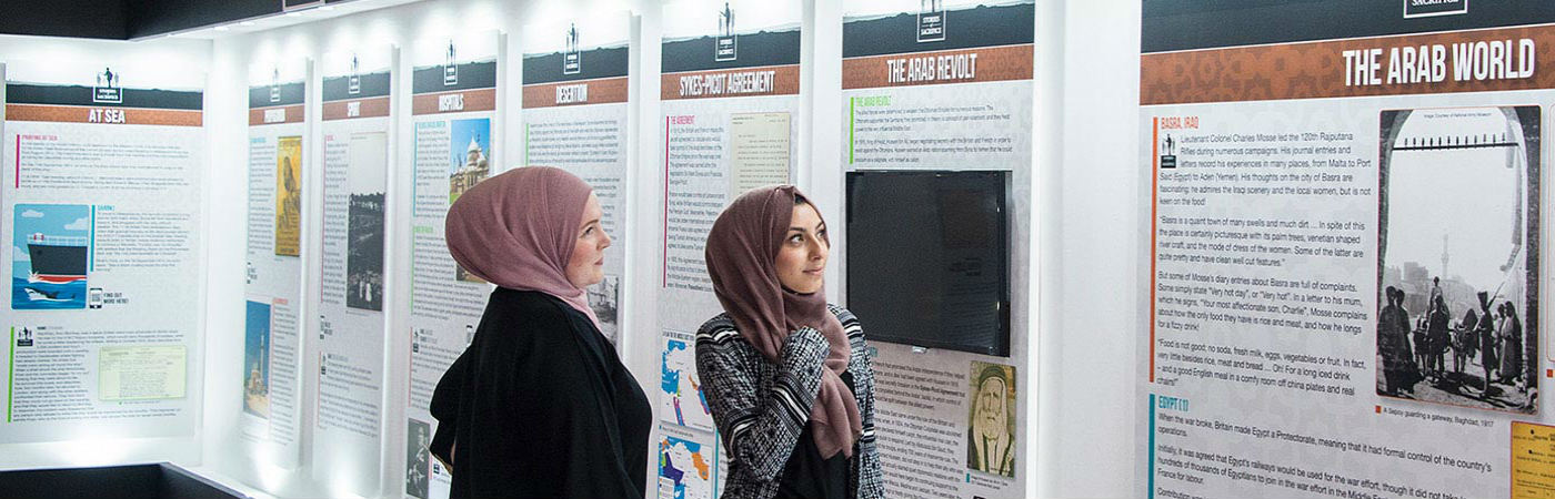 Students observing an Arabic  museum exhibition