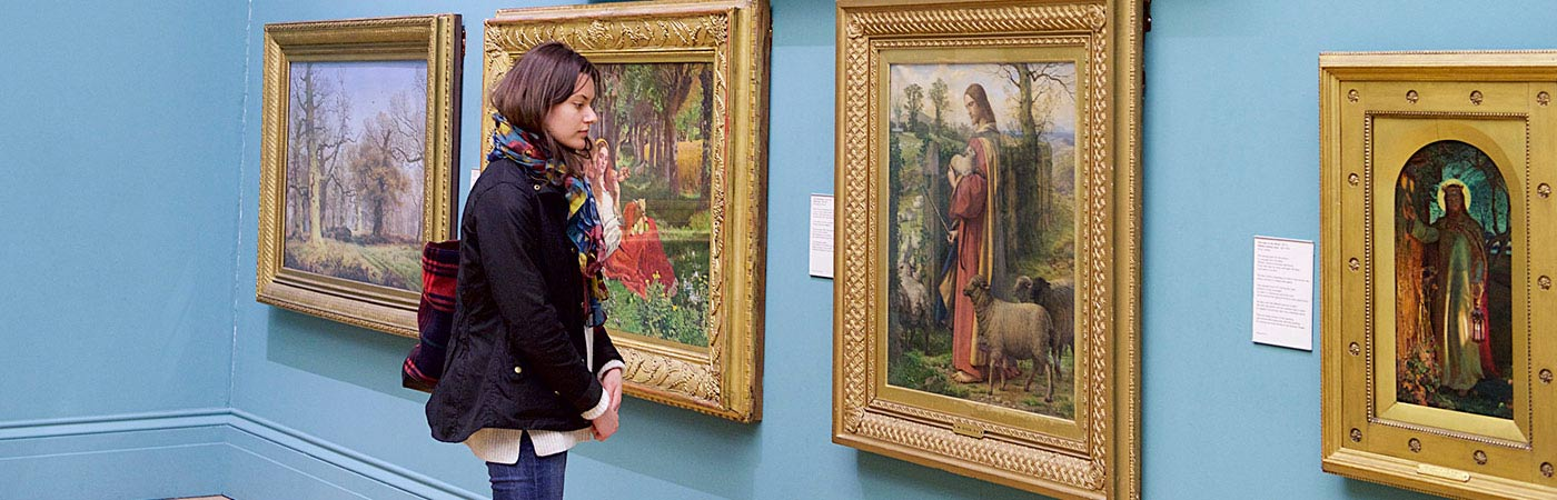 Student examining painting in Manchester Art Gallery