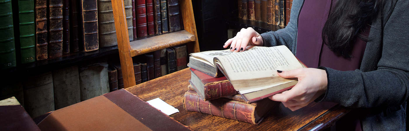 Student handling book in Chetham's Library
