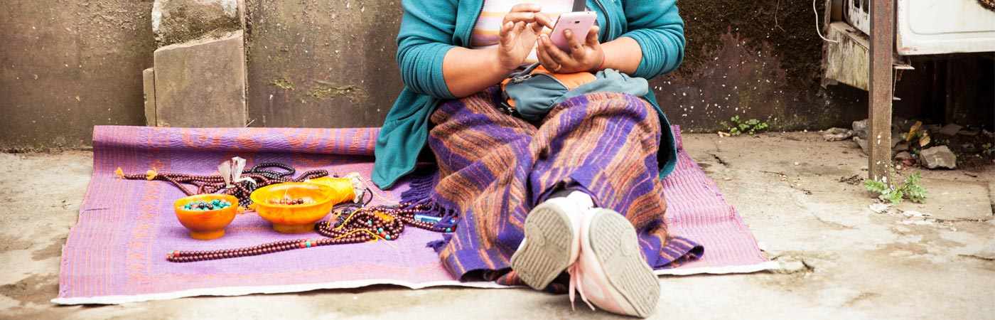 Lady in India using smartphone by roadside
