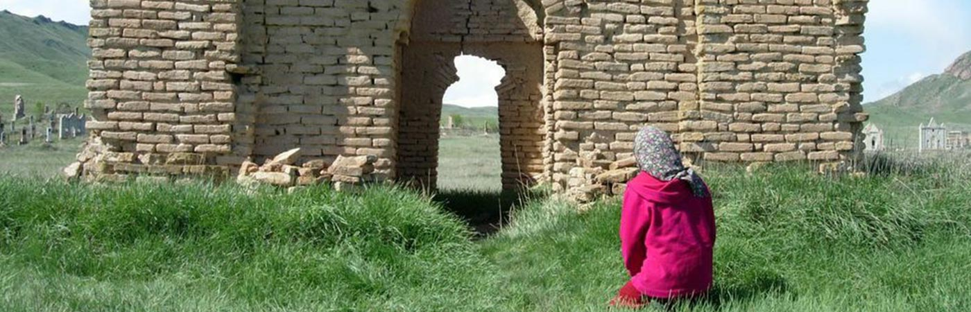A woman kneeling before a ruined building