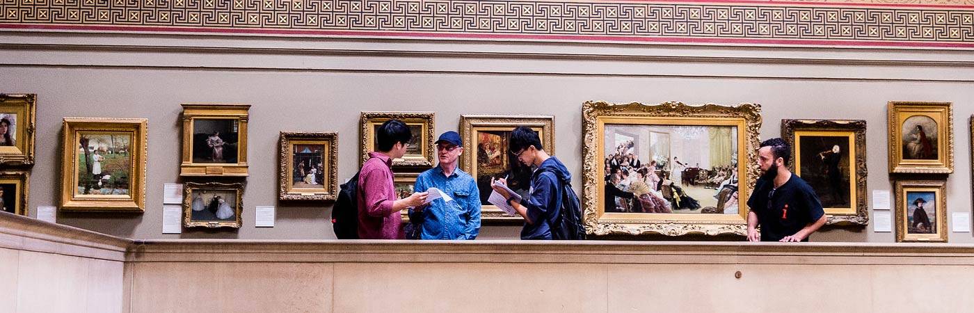 Students examining art at Manchester Art Gallery